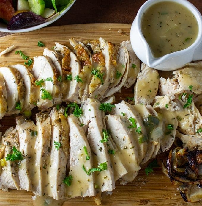 Roast Chicken Breast and Gravy on cutting board with small gravy boat on side and roasted onions
