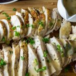 Roast Chicken Breast and Gravy on cutting board with small gravy boat on side p
