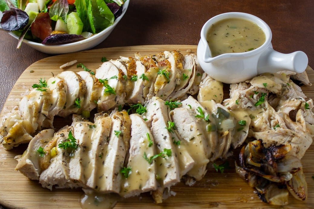 Roast Chicken Breast and Gravy on cutting board with small gravy boat on side 1
