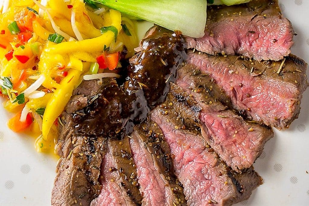 Sous Vide Flank Steak with glaze sliced on plate with mango salad