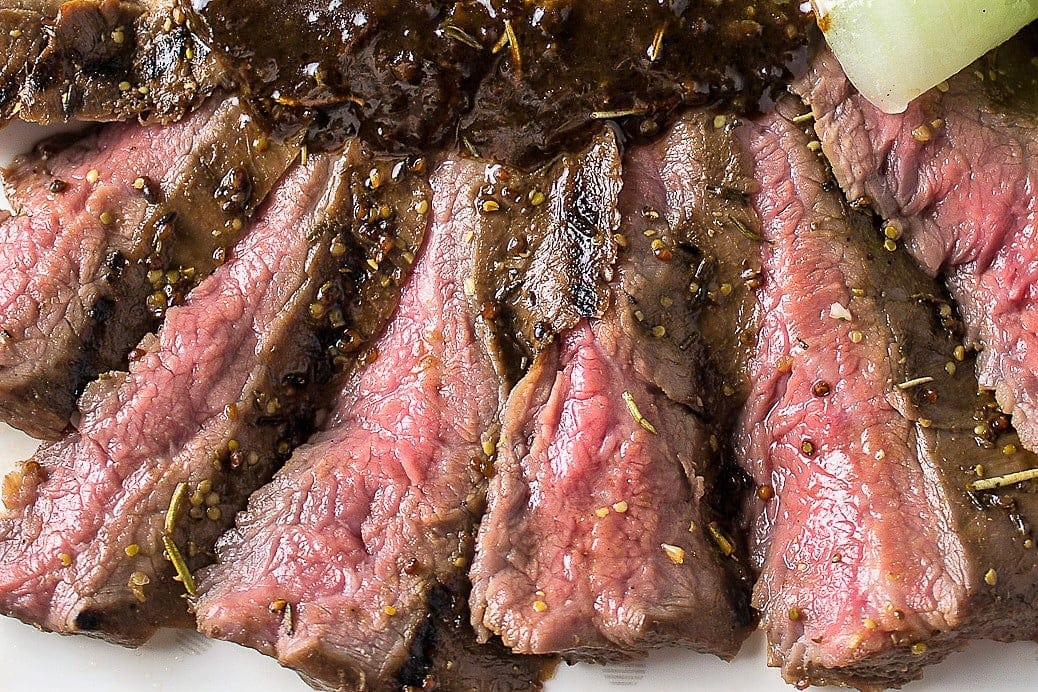 sliced sous vide flank steak on cutting board close up