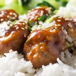 baked chicken meatballs in sauce on rice sprinkles with sesame seeds