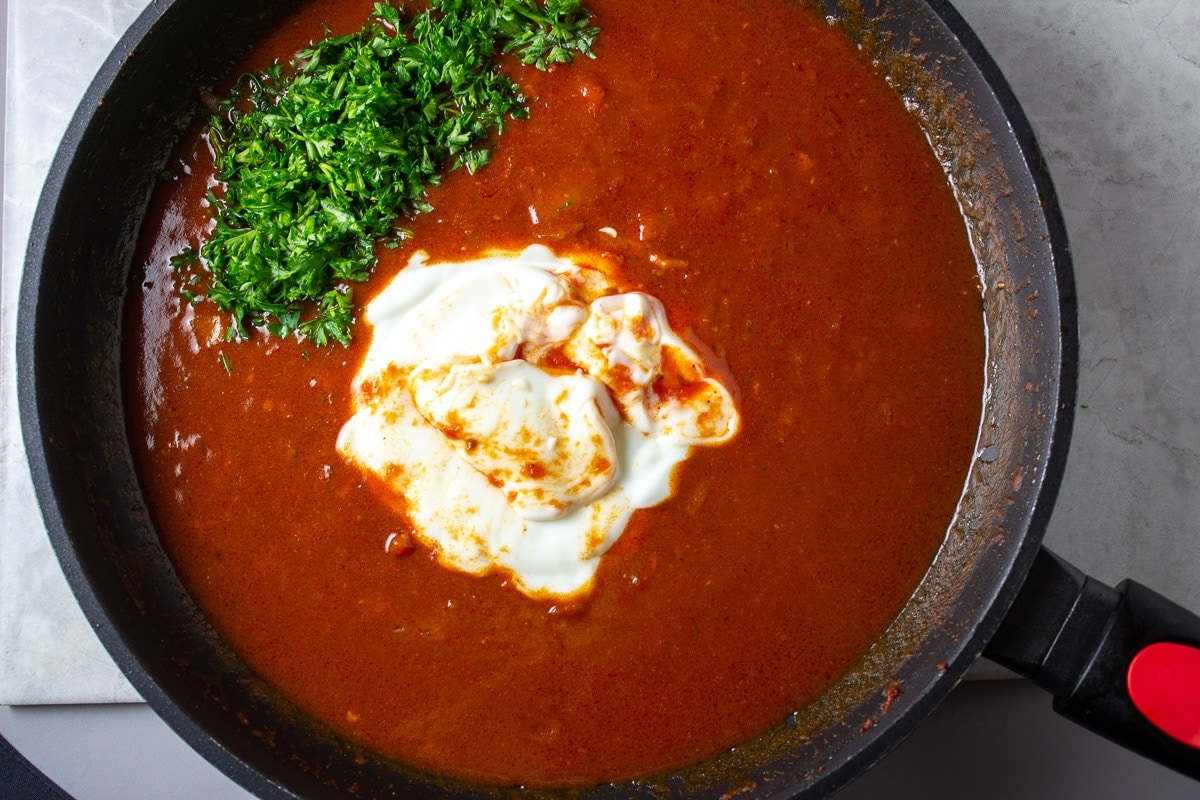 sour cream and parsley being added to paprika sauce