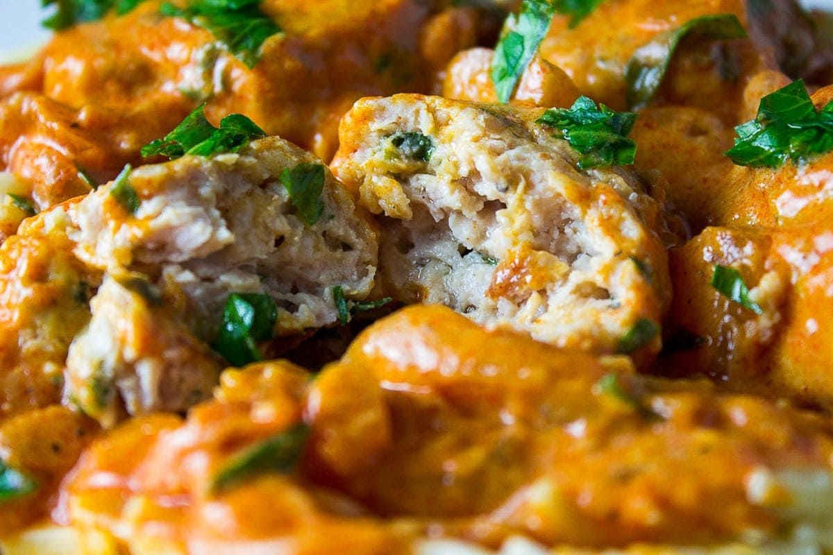 close up of cut open chicken meatball in paprikash sauce