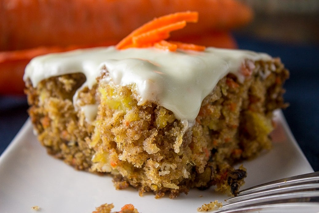 Carrot and Pineapple Cake loaded with cream cheese icing on a plate with carrots behind it.