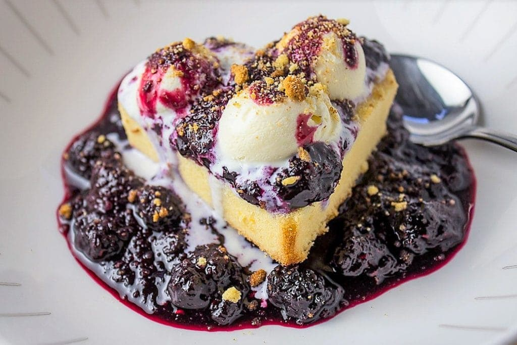 Pound Cake With Berry Sauce (the easy way) in a bowl with 3 small scoops of ice cream on top and toasted cake crumbs