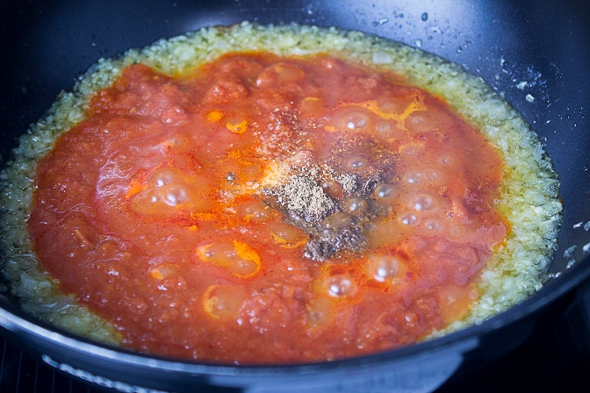 sauteed onions with tomato sauce and spices in pan