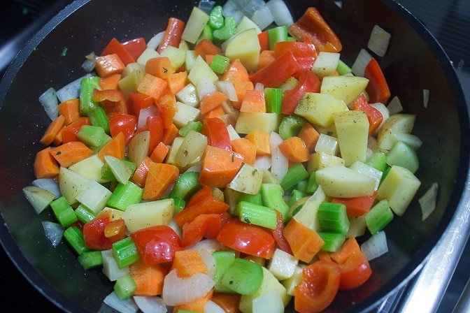 chopped onions and vegetables sauteing in pan
