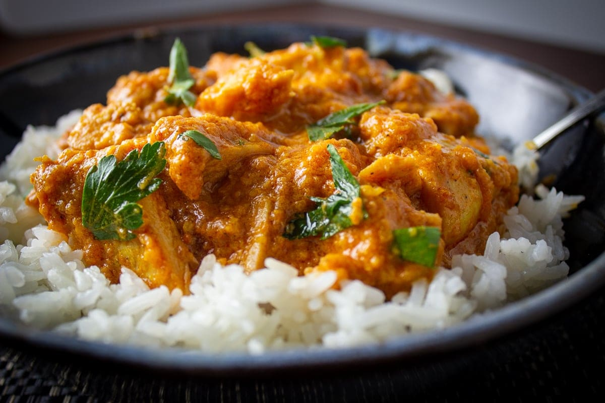 butter chicken over rice in bowl