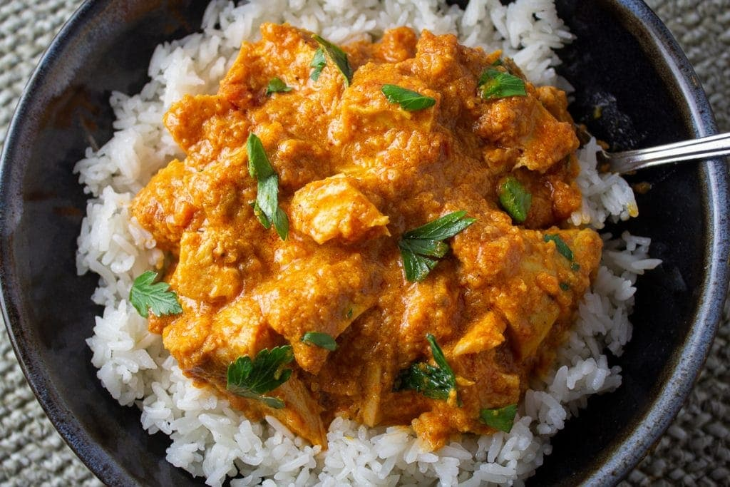 butter chicken over rice in bowl 1