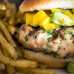 Grilled Chicken Burgers in bun with mango avocado salsa beside french fries p