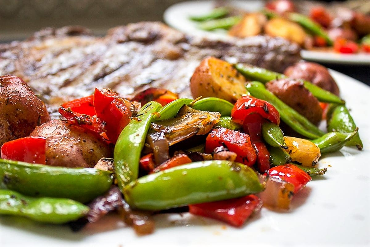 grilled veggies and potatoes on plate with steak