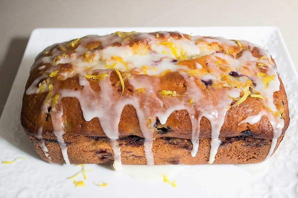 Moist Lemon-Blueberry Loaf with glaze on cutting board