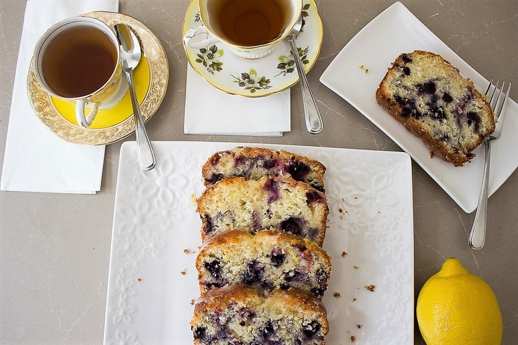 Moist Lemon-Blueberry Loaf sliced on plate with tea cups beside it