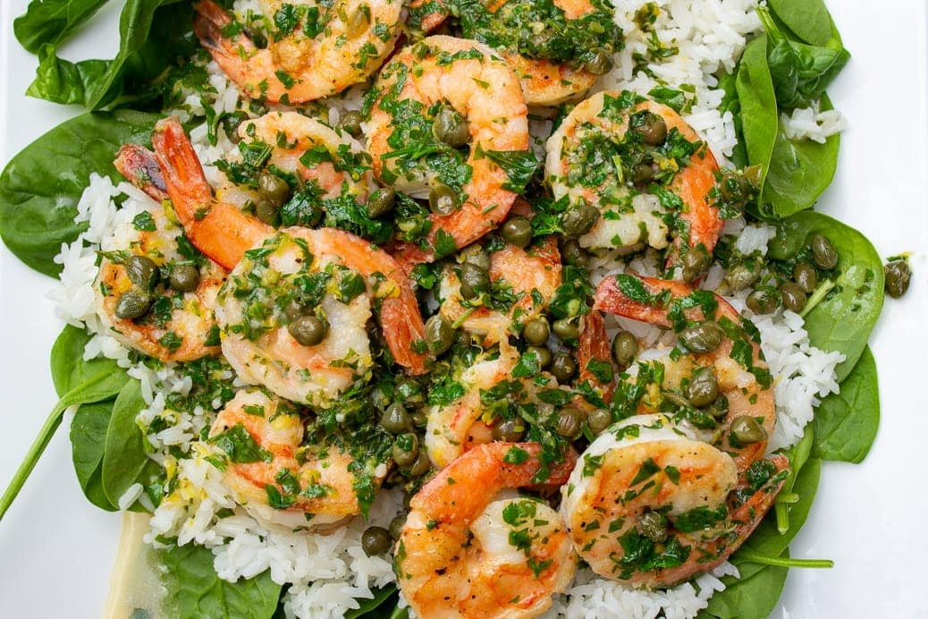 shrimp piccata over spinach and rice on plate