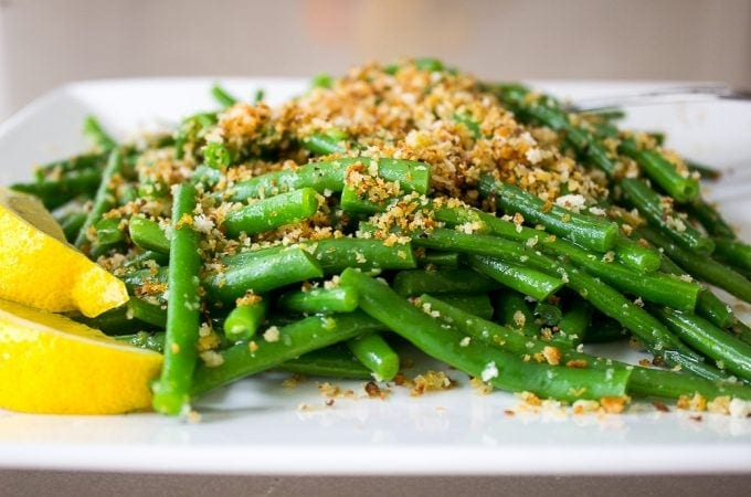 green beans with lemon garlic panko and lemon wedges on plate f