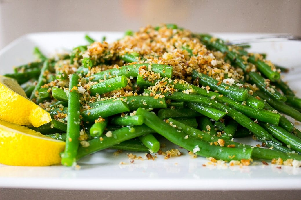 green beans with lemon garlic panko and lemon wedges on plate f