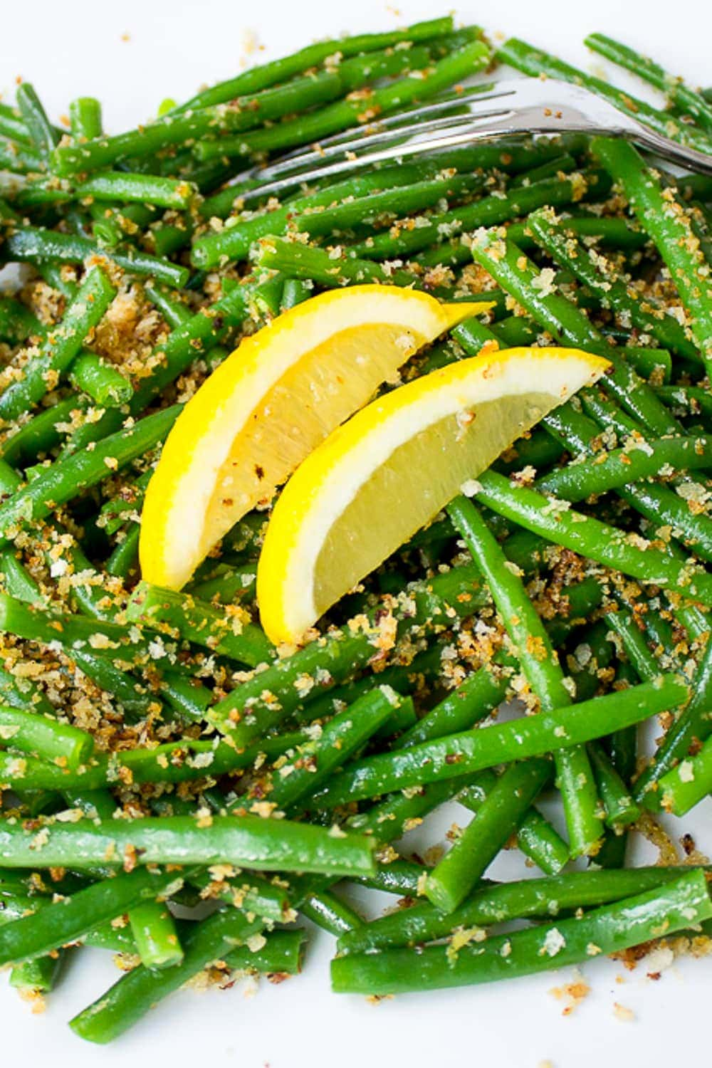green beans with lemon garlic panko on a plate with lemon wedges p