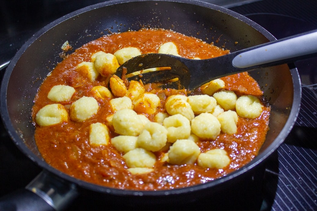 gnocchi added to Indian sauce in pan