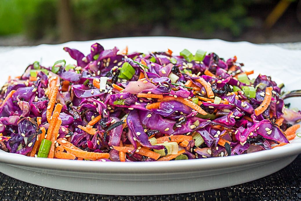 Grilled shredded cabbage with julienne carrots, green onion, sesame seeds and dressing on a platter. 1