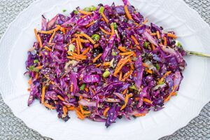 Grilled shredded cabbage with julienne carrots, green onion, sesame seeds and dressing on a platter.