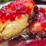 homemade strawberry jam on two scones on a plate p p