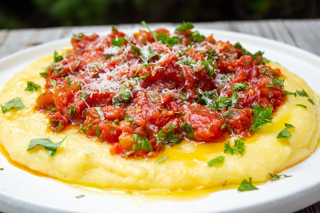 Creamy polenta on a plate with tomato herb salad