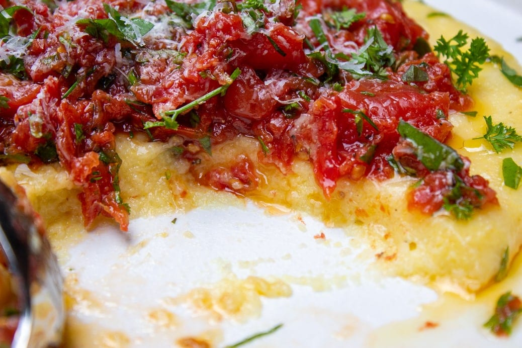 Creamy polenta on a plate with tomato herb salad with piece cut off showing inside