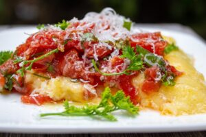 plate of polenta topped with tomato herb salad f