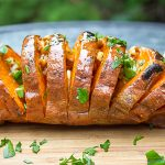 Grilled Hasselback Sweet Potato on cutting board with maple pecan drizzle f