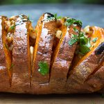 Grilled Hasselback Sweet Potatoes on cutting board middle part showing