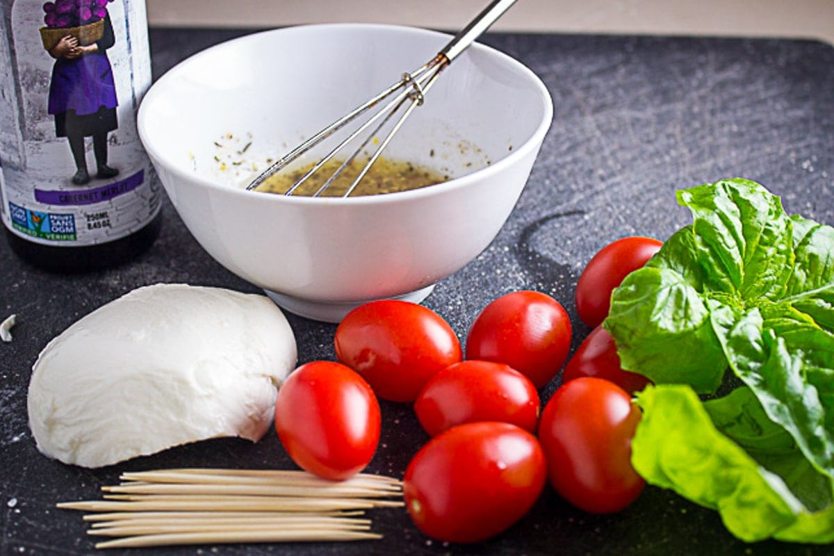 marinade in bowl, cheese, cherry tomatoes, toothpicks, basil leaves