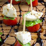 mini caprese skewers on cutting board with balsamic reduction drizzle p