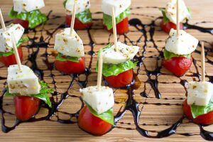 Mini Caprese skewers on cutting board with balsamic reduction drizzle f