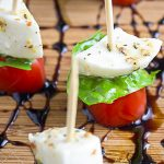 mini caprese skewers on cutting board with balsamic reduction drizzle p1