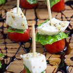 mini Caprese appetizers on toothpicks sitting on cutting board drizzled with balsamic reduction