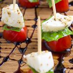 mini caprese skewers on cutting board with balsamic reduction drizzle p2
