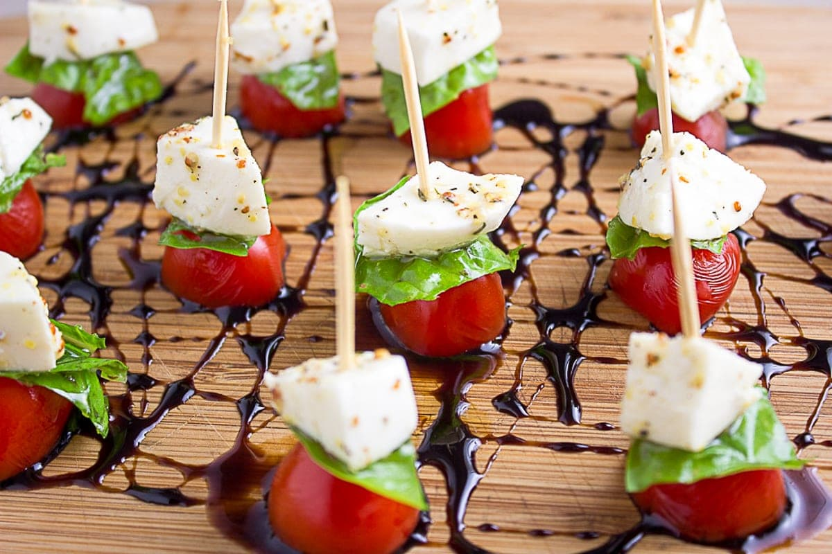 mini caprese skewers on cutting board with balsamic reduction drizzle 4
