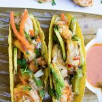 2 Grilled shrimp tacos with coconut lime chili sauce on platter p