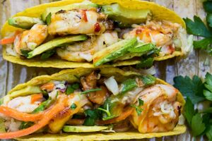 2 grilled shrimp tacos all dressed with plate of shrimp and sauce beside them