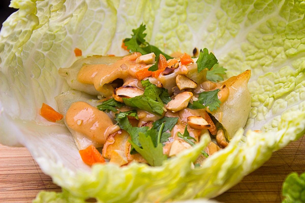 lettuce wrap with dumpling on cutting board