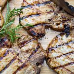 grilled marinated pork chops on cutting board with sprig of rosemary p