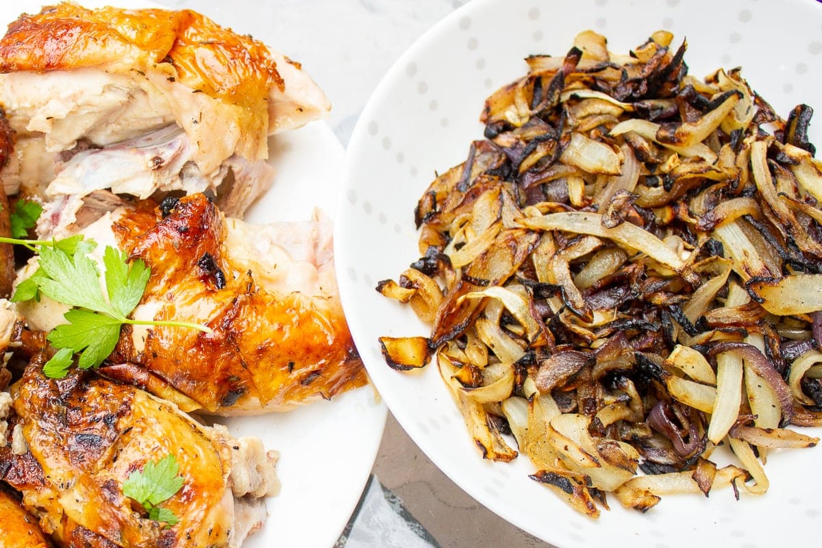 bowl of charred onions beside plate of grilled chicken