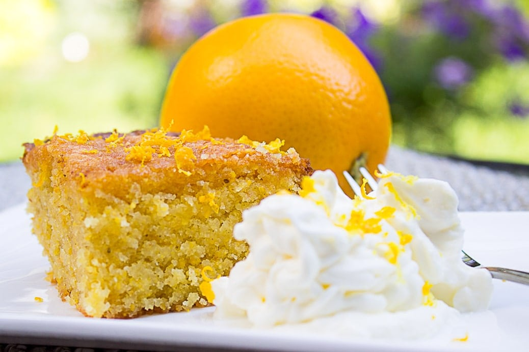 piece of orange polenta cake on plate with side of whipped cream 2