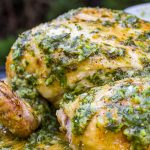 spatchcocked Chicken With Herb Garlic Lemon Smear on top and on cutting board p