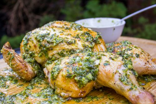 spatchcocked Chicken With Herb Garlic Lemon Smear on top and on cutting board