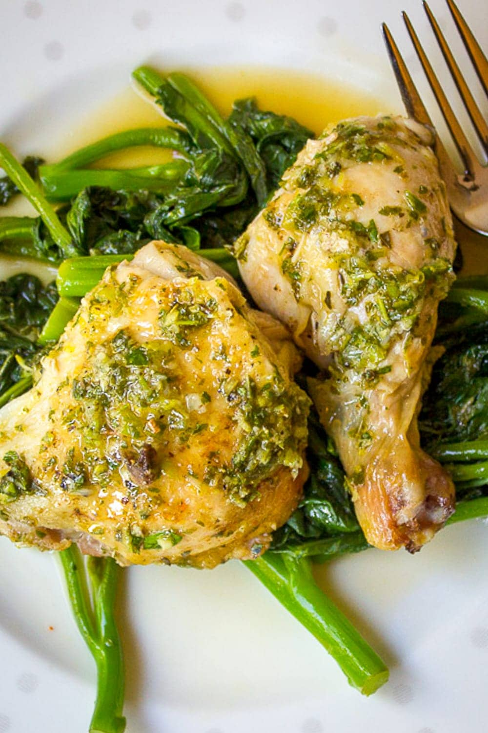 two pieces of lemon herb chicken over Chinese broccoli on a plate