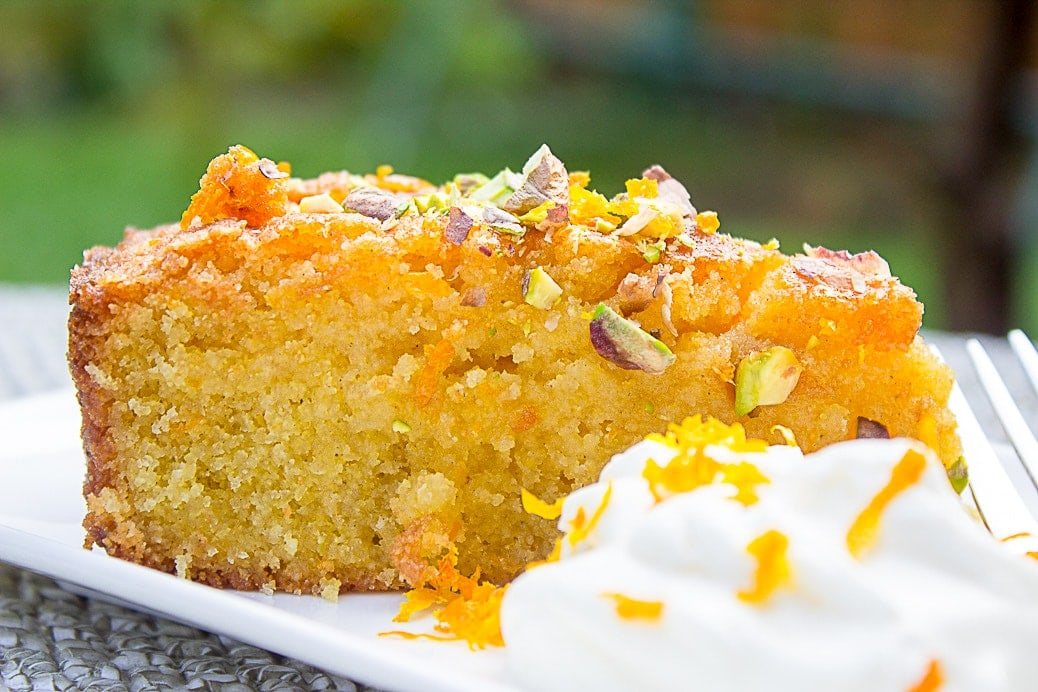piece of orange polenta cake on plate with side of whipped cream