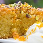 piece of orange polenta cake with whipped cream on the side p