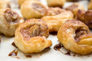 several mini glazed cinnamon puff pastry rolls on plate f